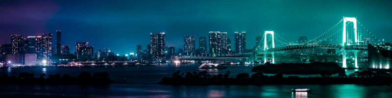 Neon lights shining out from a dark city scape.